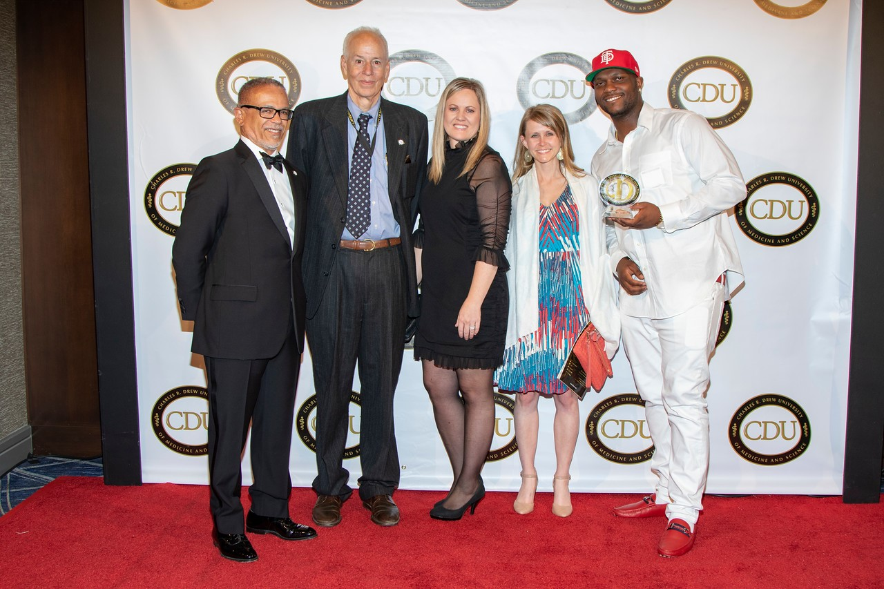 "Pictured above: Dr. David Carlisle, CDU President and CEO; Dr. Ronald Edelstein, Senior Associate Dean of the College of Medicine, Annika Borvansky, Managing Director of AOE Consulting; Sarah Porter, Program Manager at AOE Consulting; and Brandon Tiffith, son of Honoree Anthony ""Top Dawg"" Tiffith, Chief Executive Officer of Top Dawg Entertainment."